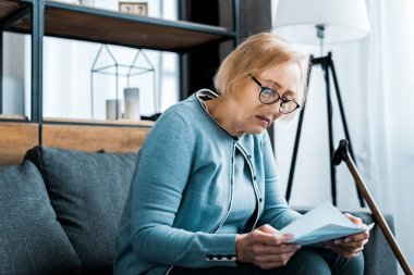 senior woman in glasses sitting on couch and holding tax form at home