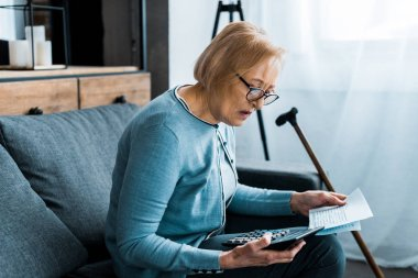 senior woman sitting on couch with calculator and counting bills at home