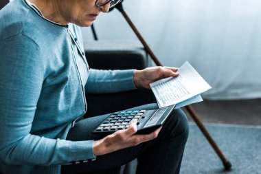 cropped view of senior woman sitting on couch with calculator and counting bills at home