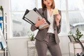 Fotografie cropped view of businesswoman holding folders and sticky note with later lettering in office