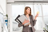 Fotografie attractive businesswoman holding folders and looking at sticky note with later lettering in office
