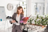 Fotografie beautiful businesswoman holding folders and reading magazine while standing in office