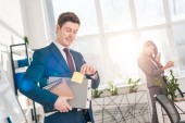Fotografie businessman holding folders and sticky note with later lettering in office with female coworker on background
