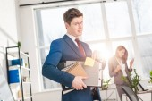 Fotografie handsome businessman holding folders and sticky note with later lettering in office with female coworker on background