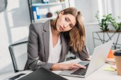 tired attractive businesswoman sitting near laptop in office