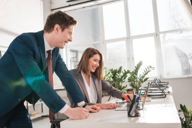 happy businesswoman laughing with coworker near laptop in office