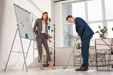 attractive businesswoman standing with hand in pocket near handsome man playing mini golf in office