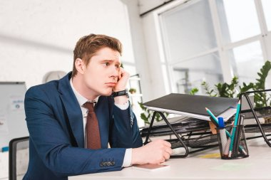 bored businessman sitting near document tray in office