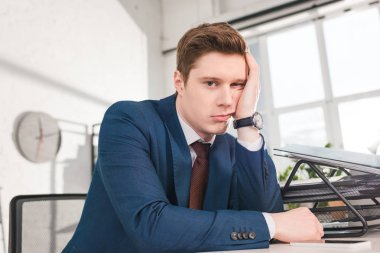 bored businessman sitting and looking at camera in office