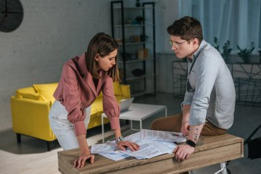 woman standing near man in glasses near charts and graphs