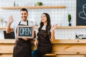 Fotografie cashier and barista greeting and holding chalkboard with open lettering near wooden bar counter in coffee house