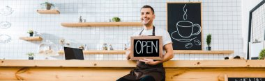 handsome cashier in brown apron sitting on chair near wooden bar counter and holding chalkboard with open lettering in coffee house