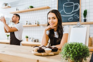 attractive brunette waitress standing behind bar with cupcakes on wooden tray wile barista holding cup in coffee house