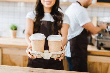 cropped view of brunette cashier standing and holding paper cups wile barista  working in coffee house