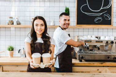 brunette cashier standing and holding paper cups wile man making coffee in coffee house