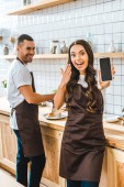 Fotografie brunette cashier showing smartphone with blank screen wile barista smiling in coffee house