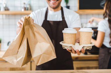 cropped view of cashier holding paper cups and bags wile brunette barista making coffee in coffee house