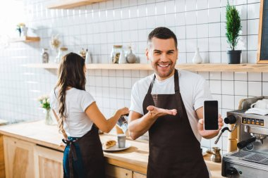 handsome cashier pointing with hand to smartphone with blank screen wile barista working in coffee house