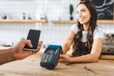 selective focus of male hand holding smartphone wile cashier standing near bar counter and holding terminal in coffee house