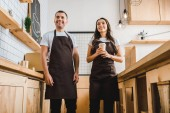 Fotografie cashiers standing and smiling behind wooden bar counter in coffee house