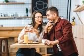 atraktivní bruneta žena a pohledný muž, sedící u stolu a při pohledu na smartphone v kavárně