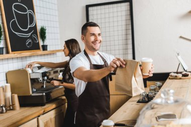 handsome cashier giving paper cup and bag wile barista making coffee behind bar counter in coffee house