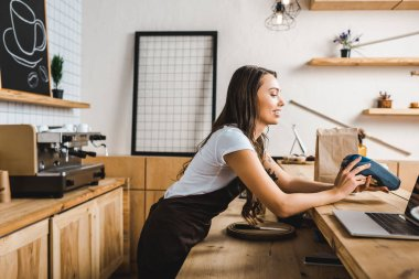 attractive cashier standing in brown apron and holding terminal behind bar counter in coffee house