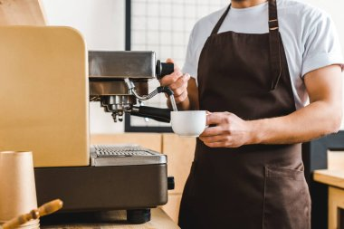 cropped view of handsome barista holding cup and making coffee with machine in coffee house