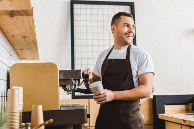 handsome barista holding cup and making coffee with machine in coffee house