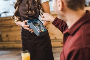 cropped view of waitress holding terminal wile handsome man sitting at table and paying with credit card in coffee house