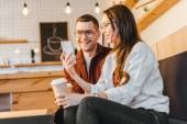 atraktivní žena a pohledný muž sedí na gauči, držení mály a chtějí smartphone v kavárně