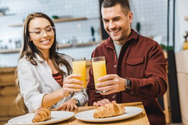 selective focus of glasses with juice in woman and man hands sitting at table with croissants in coffee house