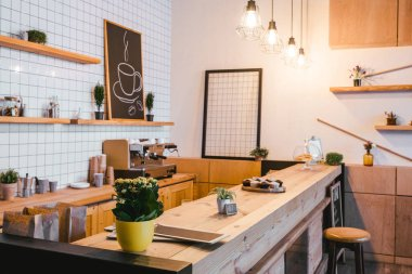 wooden brown bar counter with plants and cupcakes in coffee house