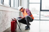 hezký hasič v helmě sedí u hasicích přístrojů a držení schránky