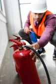 selective focus of red extinguishers near fireman with clipboard in hand