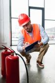 vážnou hasič v helmě psaní schránky při kontrole hasicích přístrojů
