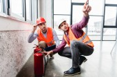 handsome fireman pointing with finger near coworker while sitting near red extinguishers