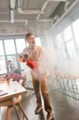 jóképű üzletember betöltő az tűzoltó és sikoltozik füst közelében kollégák hivatalban