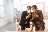 Selektivní fokus vyděšený kolegů v maskách pomocí smartphone v úřadu s kouřem