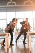 uomo daffari spaventato holding estintore vicino a colleghi mentre si cammina in ufficio con il fumo