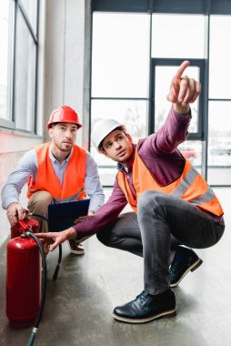 fireman pointing with finger near coworker while sitting near red extinguishers