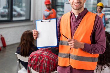 Cropped view of cheerful fireman pointing at blank clipboard with pen near coworkers giving talk on briefing on background stock vector