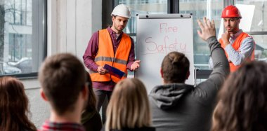 selective focus of handsome firemen in helmets giving talk on briefing near white board with fire safety lettering