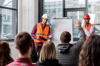 selective focus of handsome firemen in helmets giving talk on briefing near white board with fire safety lettering and looking at man raising hand
