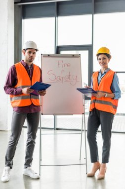 selective focus of fireman standing near attractive coworker near white board with fire safety lettering