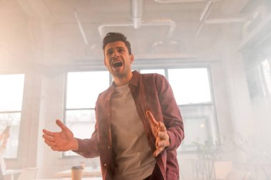 handsome businessman yelling in office with smoke
