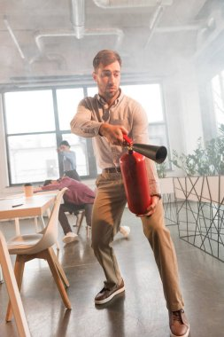 frightened businessman holding extinguisher in office with smoke near colleagues