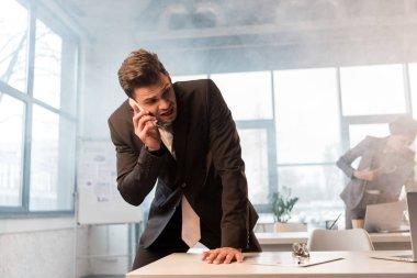 frightened businessman talking on smartphone in office with smoke near female coworker