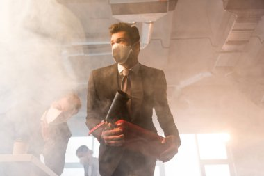 frightened businessman in mask holding extinguisher near coworkers in office with smoke