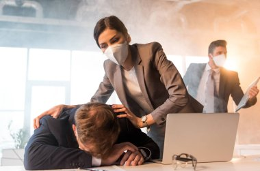 selective focus of terrified woman in mask standing near colleague lying on desk near laptop in office with smoke